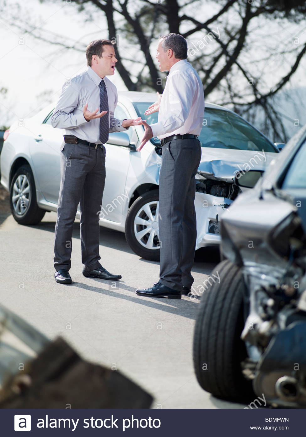 Two businessmen arguing about damaged cars - Stock Image