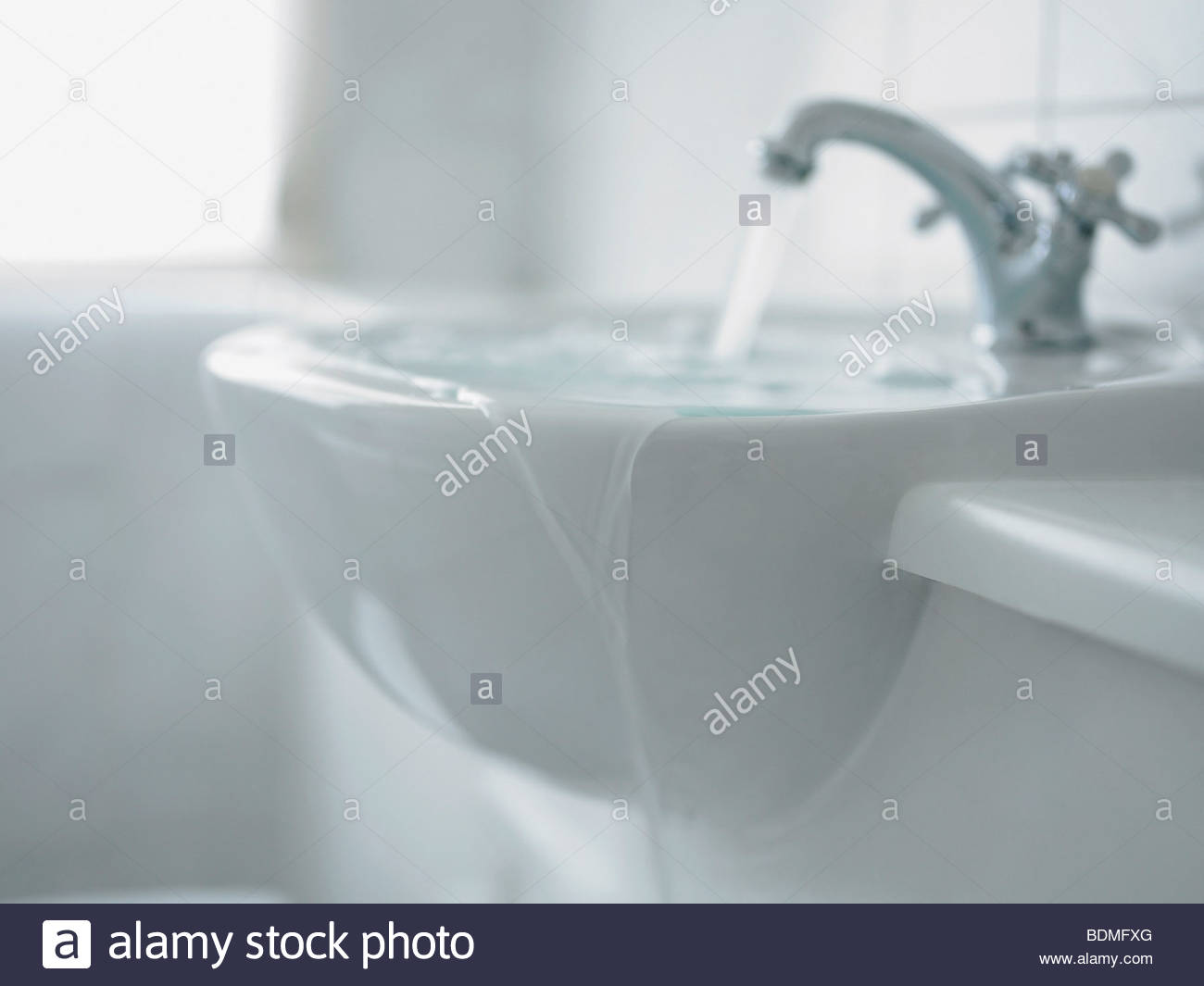Close up of overflowing bathroom sink - Stock Image
