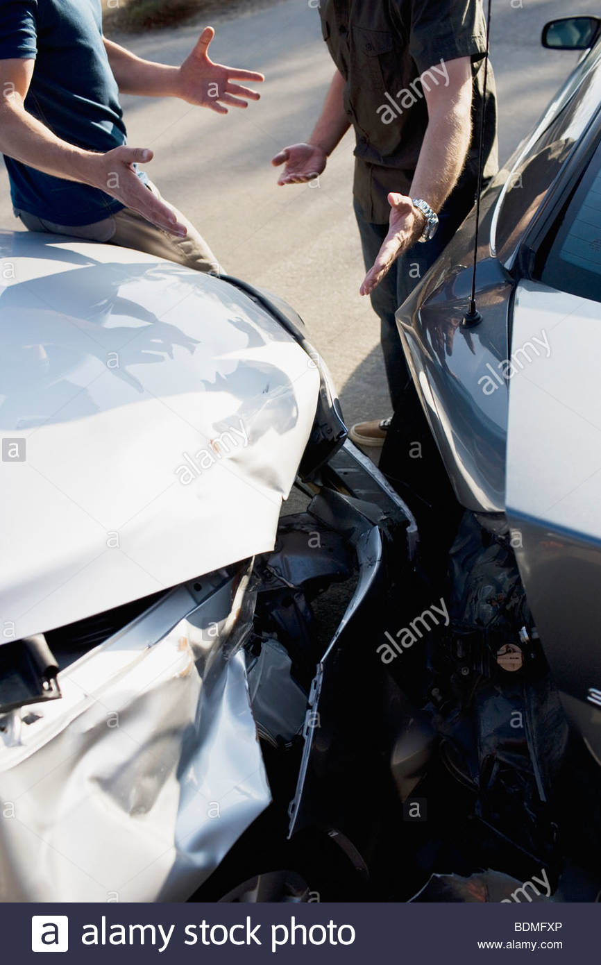 Two men arguing about damaged cars - Stock Image