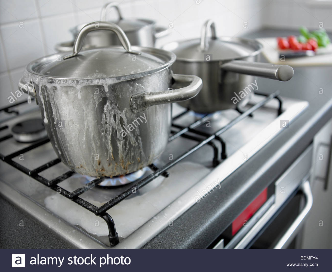 Pot boiling over in kitchen - Stock Image