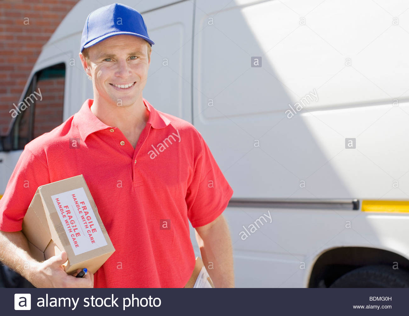Delivery man holding cardboard box - Stock Image
