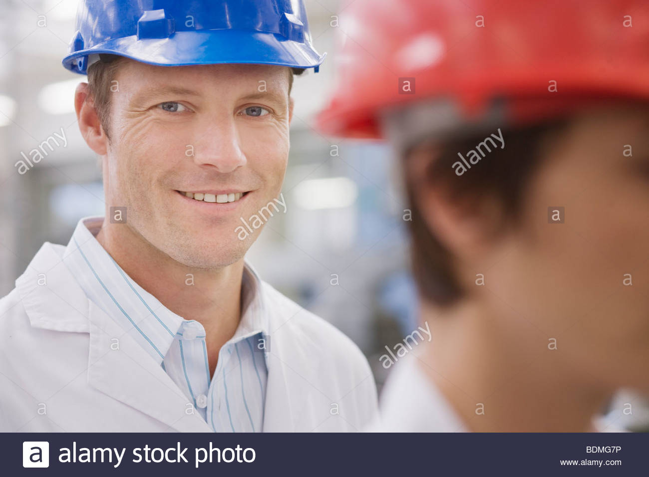 Man in hard-hat and lab coat smiling - Stock Image