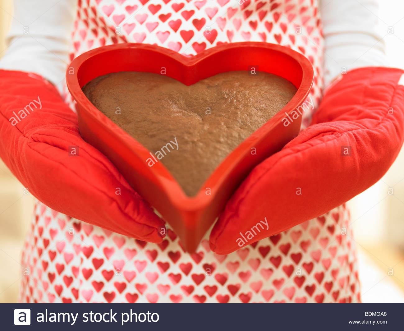 Close up of woman holding heart-shaped cake Stock Photo