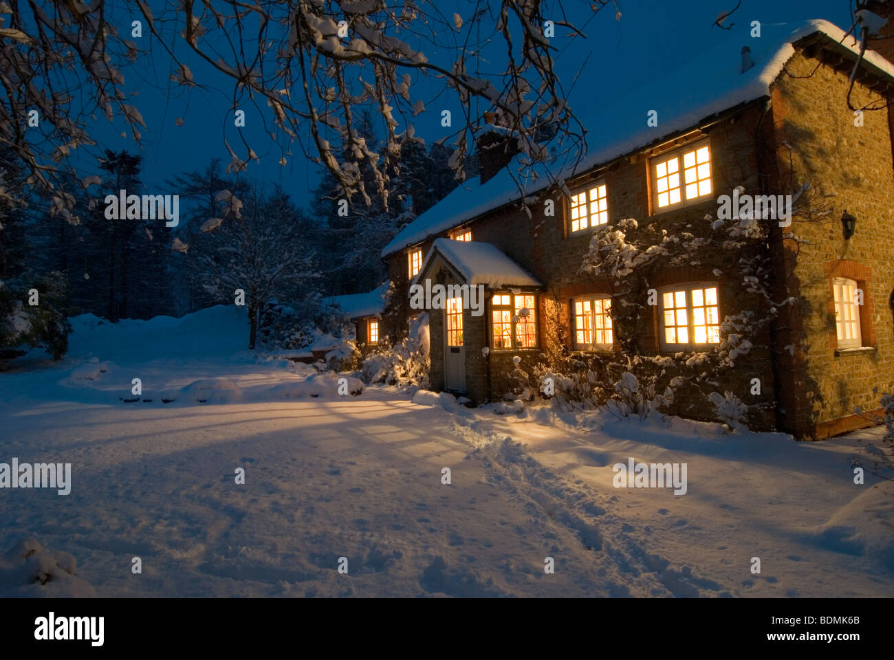 Christmas Scene Of Country Cottage As Night Begins To Fall Surrounded By Snow