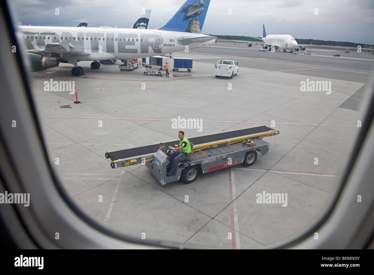 A worker drives a luggage conveyor at Anchorage International Airport - Stock Image