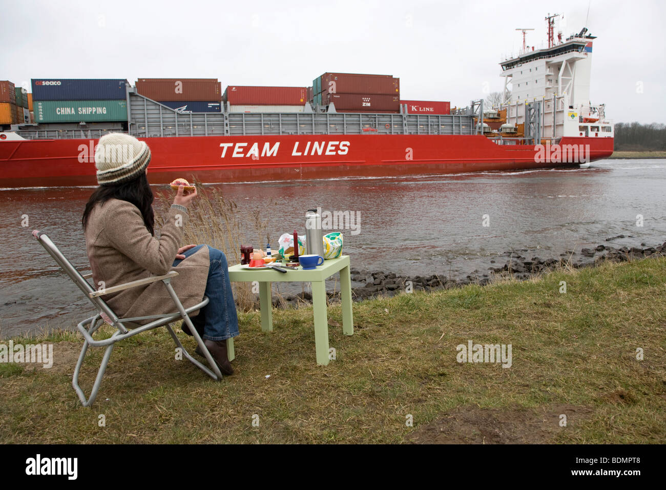 Young woman, 30-35 years, having breakfast on a damp winter day at the Kiel Canal, watching passing ships, Schleswig - Stock Image