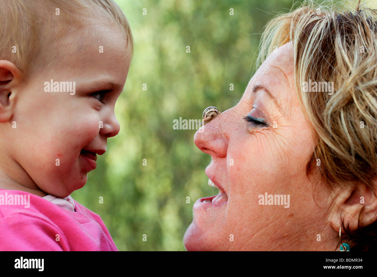 A toddler admires a snail with his mother - Stock Image