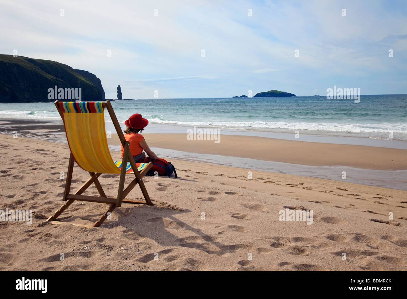 Woman on the Beach sitting on the sand near deckchair at Sandwood Bay, Sutherland in the Western Highlands of Scotland, - Stock Image