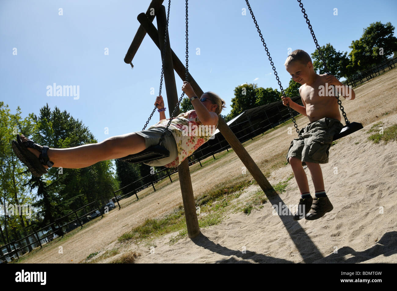 Stock photo of a mother and son playing on the swings on the playground. - Stock Image