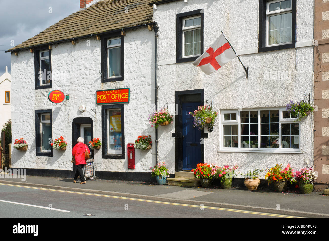 Old lady with shopping trolley at Gargrave Post Office, North Yorkshire, England, UK - Stock Image