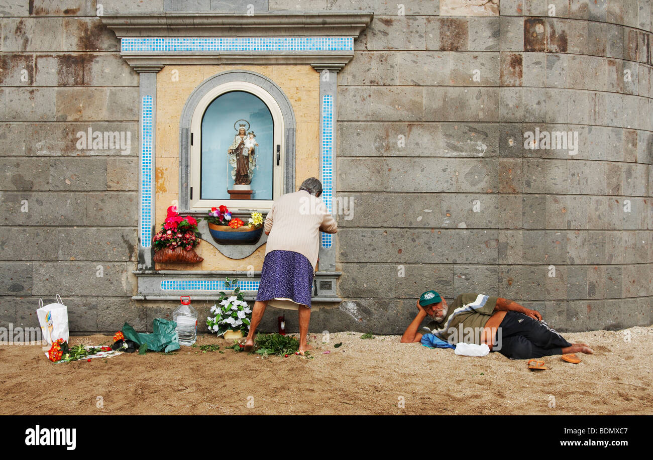 Old Spanish woman changing flowers at shrine on beach while man watches. Could be used for gender pay gap, equal Stock Photo