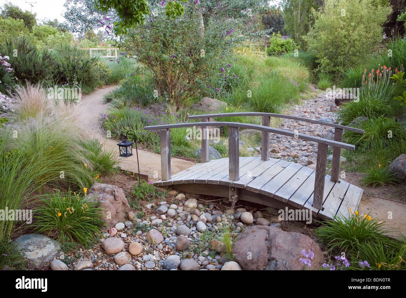 Path with bridge over dry gravel stream in California meadow garden Garden Design Dry Stream Bridge on dry stream landscape, wooden deck garden, gully garden,