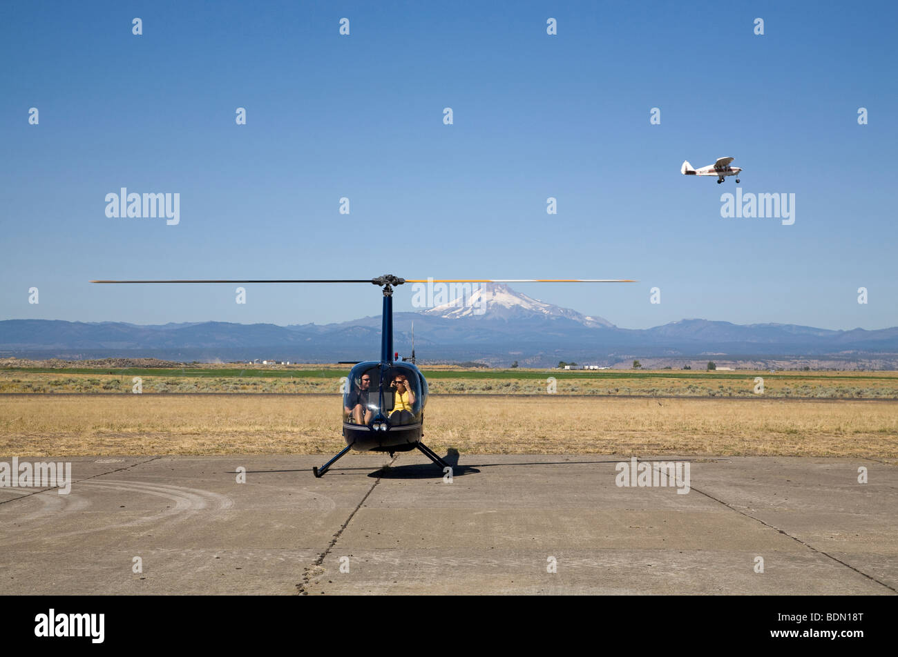 A small Cessna aircraft light plane and a light Robinson R44 helicopter at an airshow in Madras Oregon - Stock Image