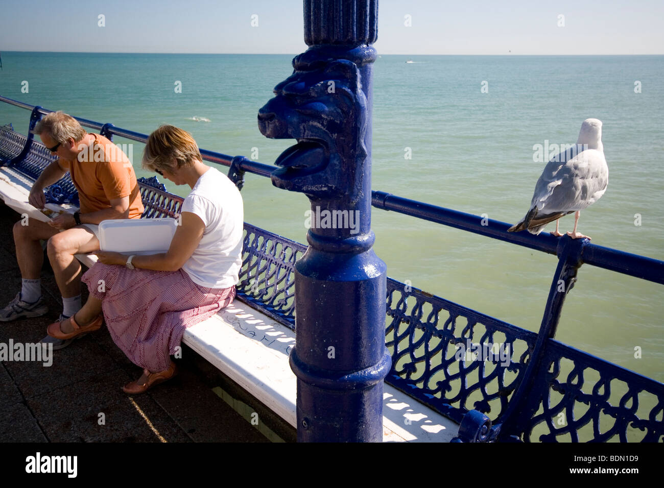 A gull waits for scraps while a couple eat their food on the pier at Eastbourne, England. - Stock Image