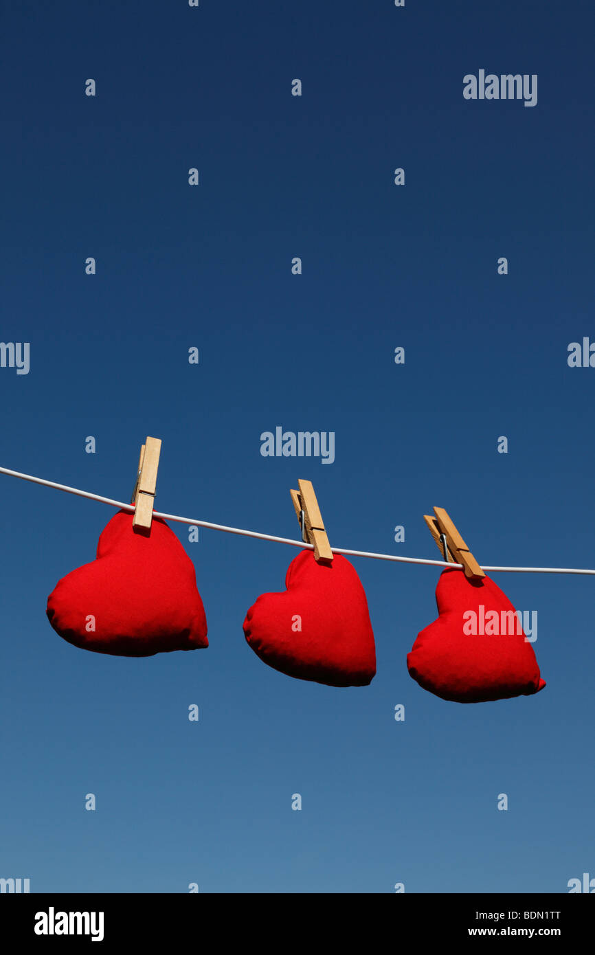 Heart shaped bean bags on a washing line against a summer sky (version with clouds Ref BDNR52) - Stock Image