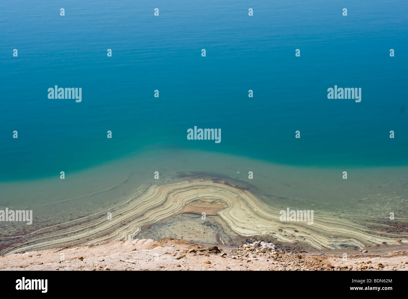 Mineral deposits ring the eastern shore of the Dead Sea in Jordan. - Stock Image