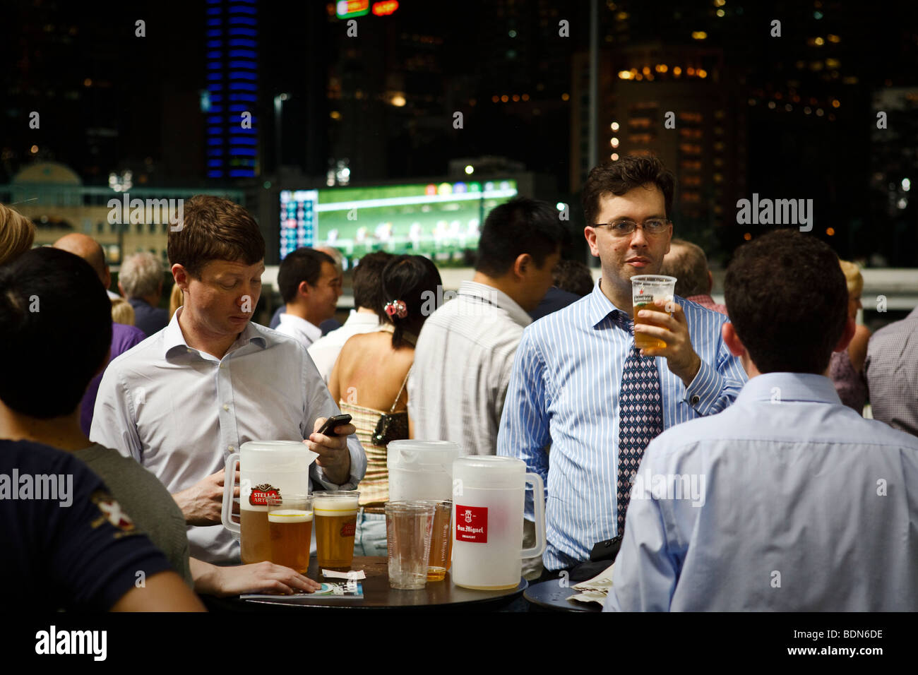 Expat punters enjoy a night out at a night horse racing event at the Happy Valley race course in Hong Kong. - Stock Image