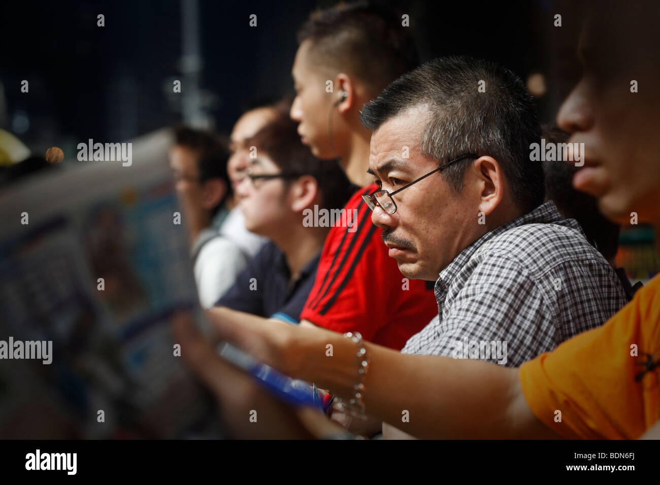 Punters study the race form at a night horse racing event at the Happy Valley race course in Hong Kong. - Stock Image