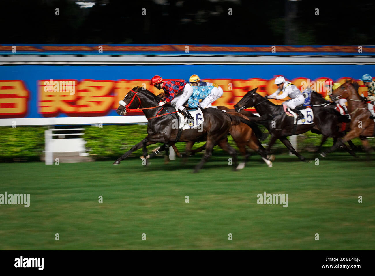 A final gallop to the finish at a night horse racing event at Happy Valley race course in Hong Kong. - Stock Image