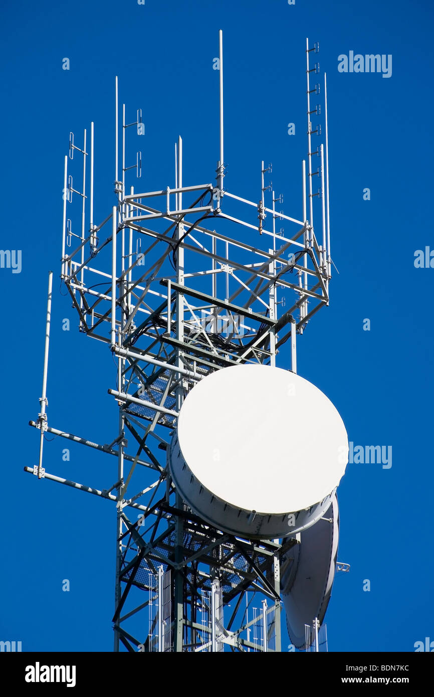 a communication tower silhouetted against blue sky. There is a large dish at the front suitable to add copy or your Stock Photo