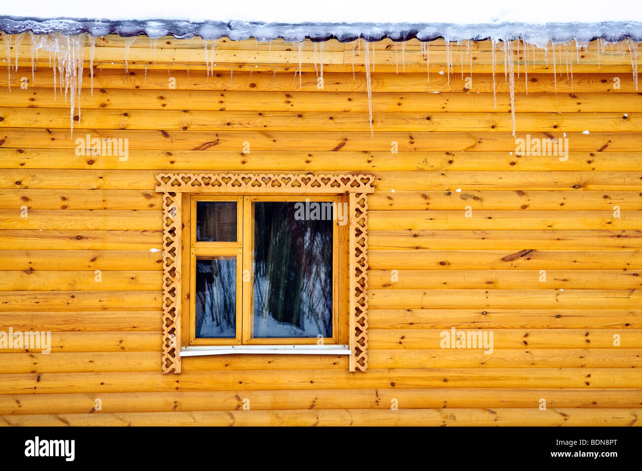 Country cottage house pine balk wall with window and icicle - Stock Image