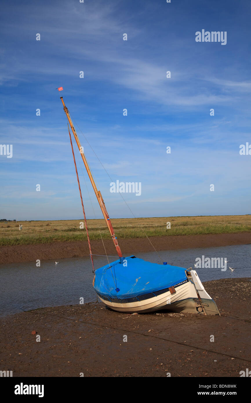 A sailing boat aground on the side of new cut channel at Blakeney North Norfolk England - Stock Image