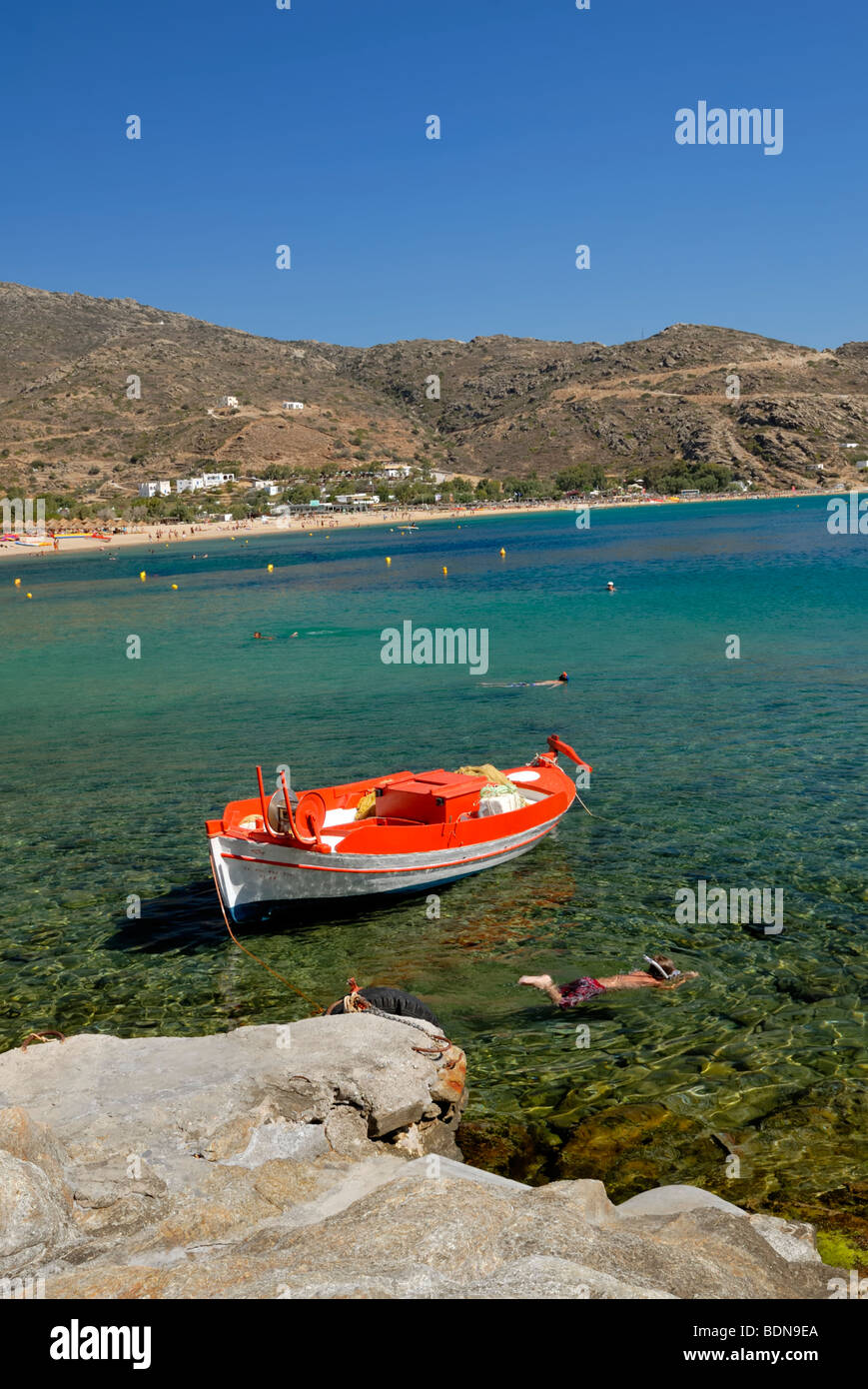 Children are snorkling near the fishing boat pier in the Mylopotas beach, one of the best beaches to be found anywhere in Greece Stock Photo