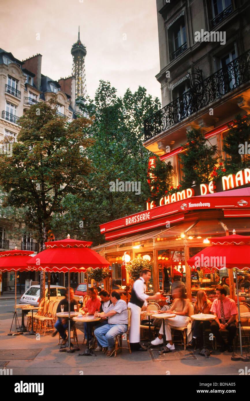 Le Champ De Mars Restaurant with patrons on Ave de la Bourdonnais in Paris under Eiffel Tower at dusk Stock Photo