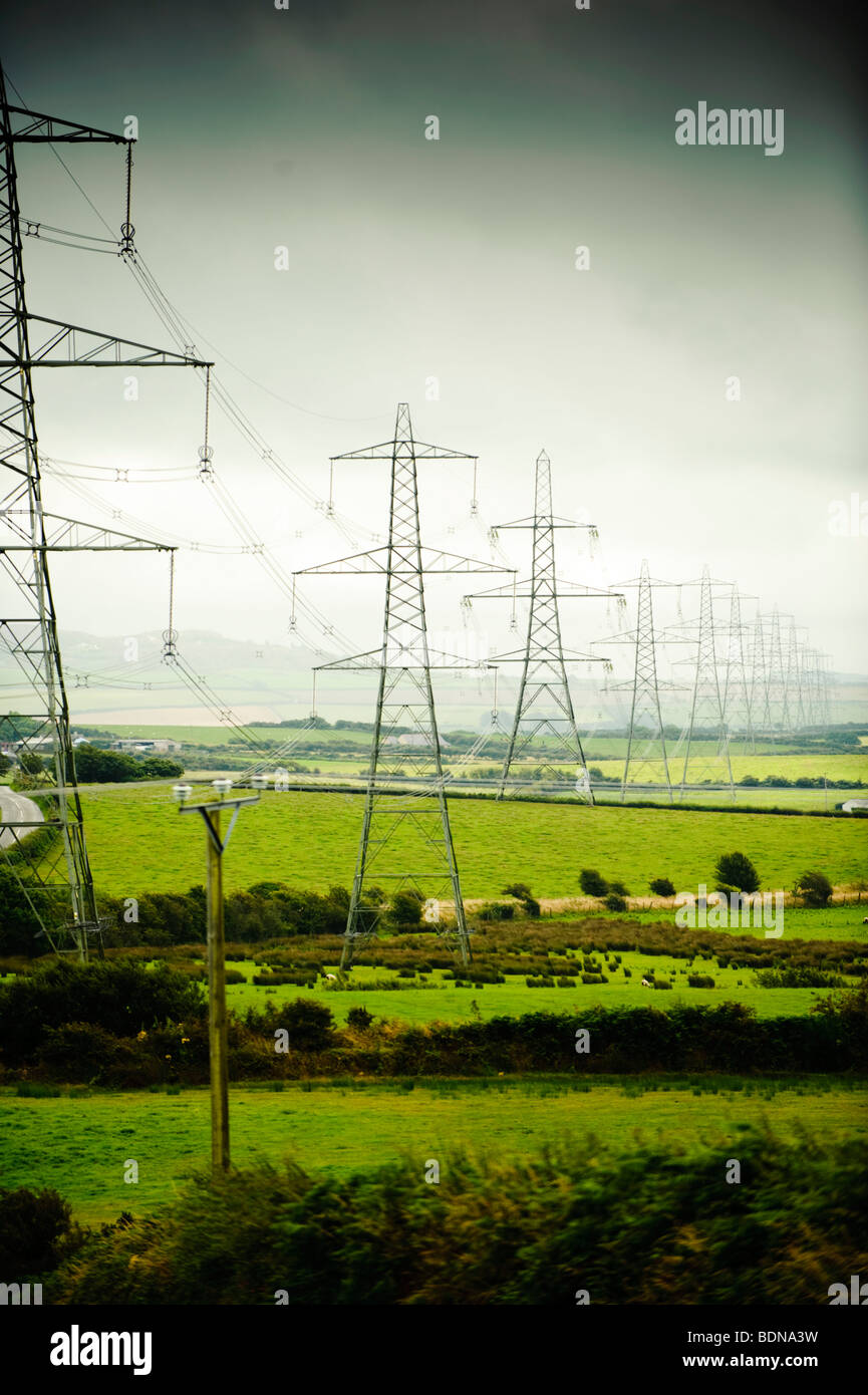 A row line of national grid Electricity pylons marching across the rural landscape of Anglesey, north wales UK - Stock Image