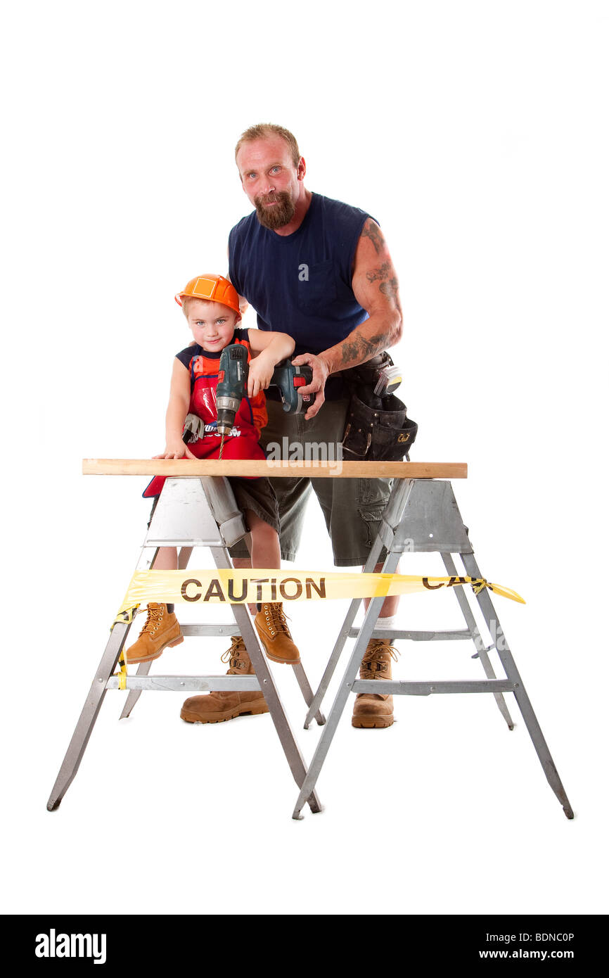 Caucasian dad is teaching cute son with construction helmet how to drill a hole in a wooden plank, isolated. - Stock Image