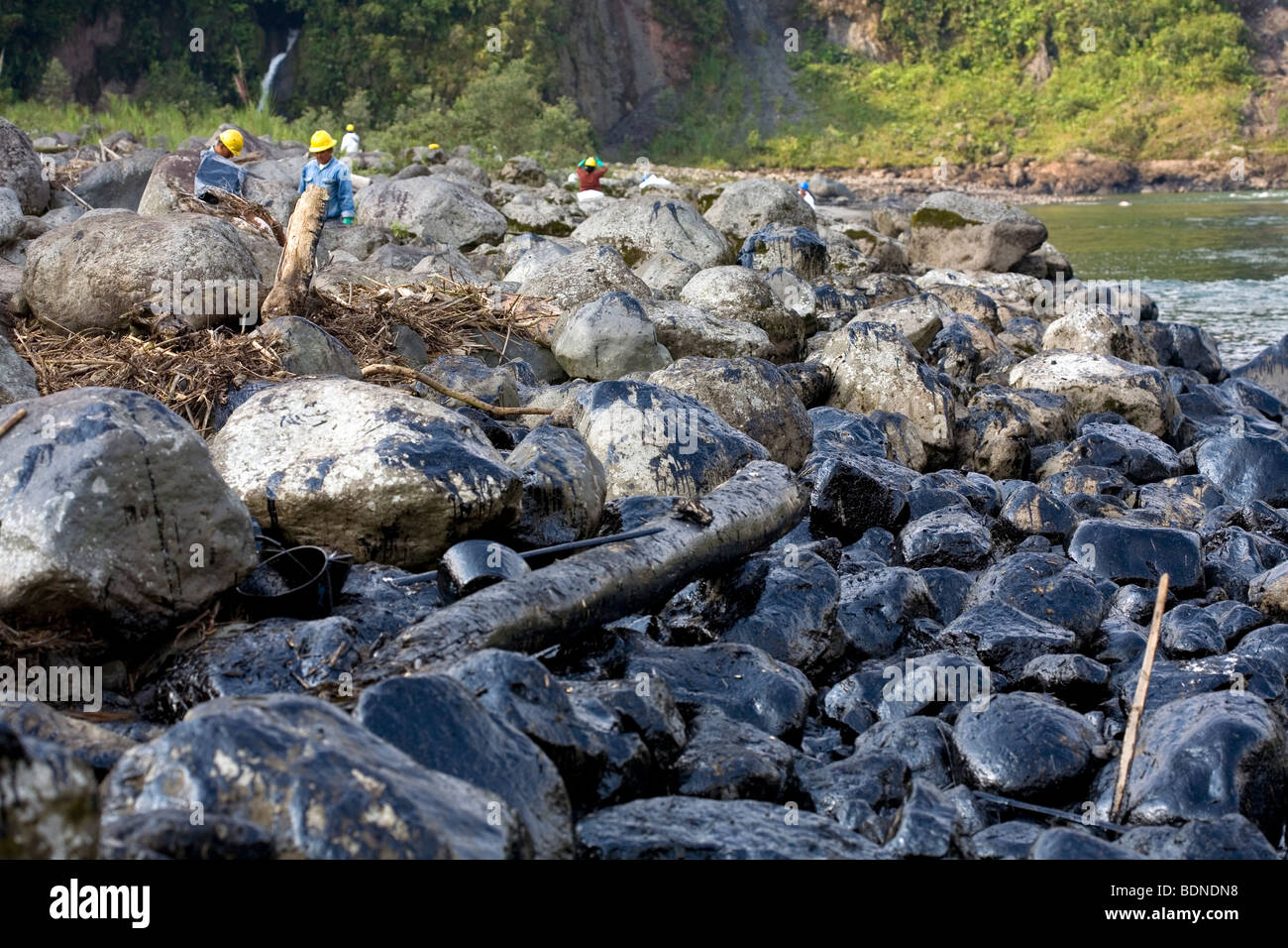 Oiled rocks at the edge of an Amazonian river after an oil spill - Stock Image