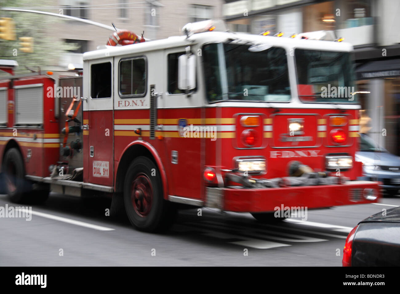 A fast moving (and BLURRY) Fire Department New York fire truck passing on a busy street, New York, United States - Stock Image