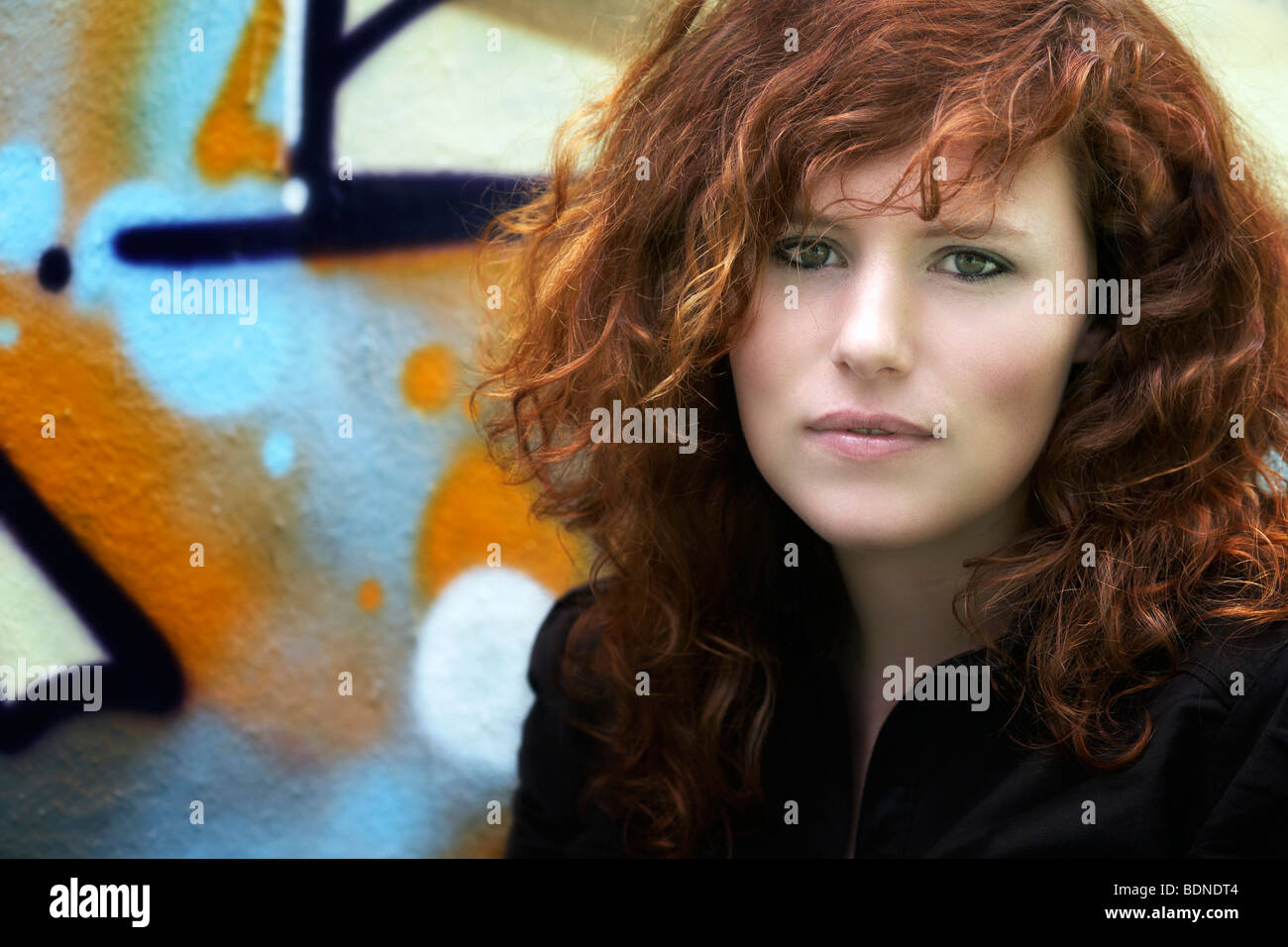 Portrait of a young red-haired woman, in front of a graffiti-sprayed wall - Stock Image