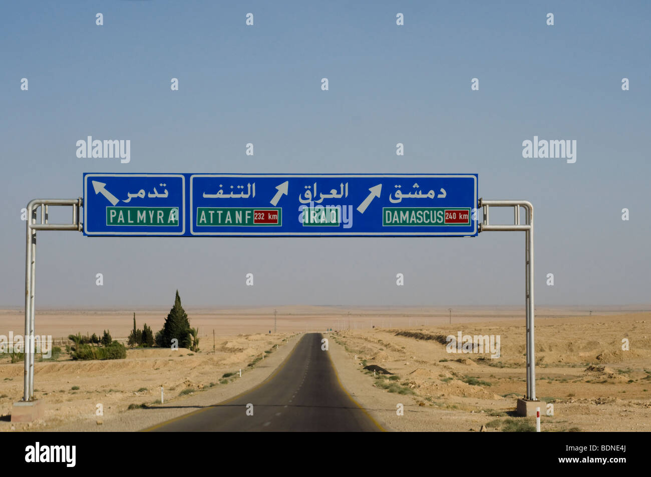 Road signs along a Syrian highway point the way to Iraq and the Syrian capital of Damascus. - Stock Image