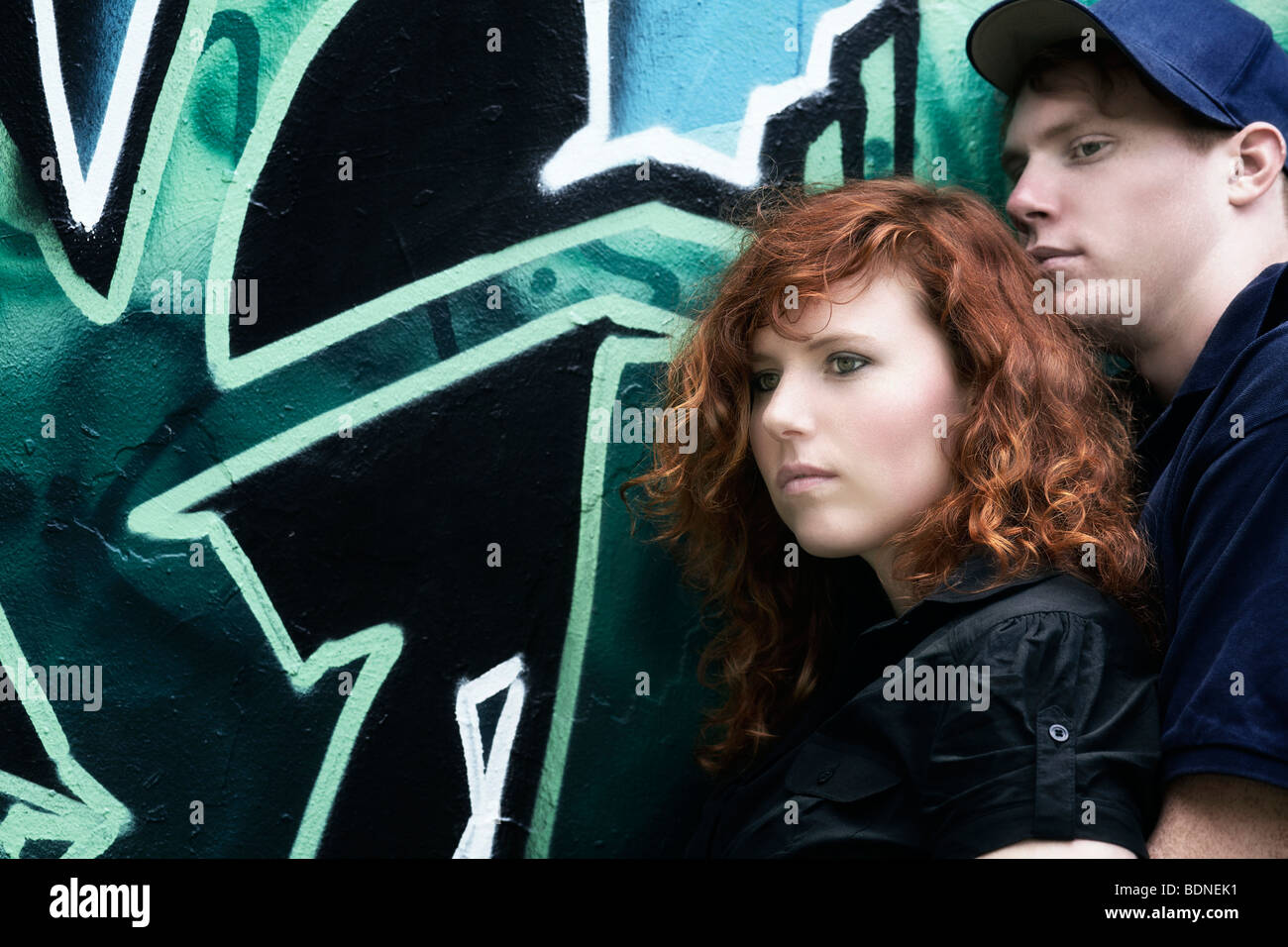 Young couple in front of a graffiti-sprayed wall - Stock Image