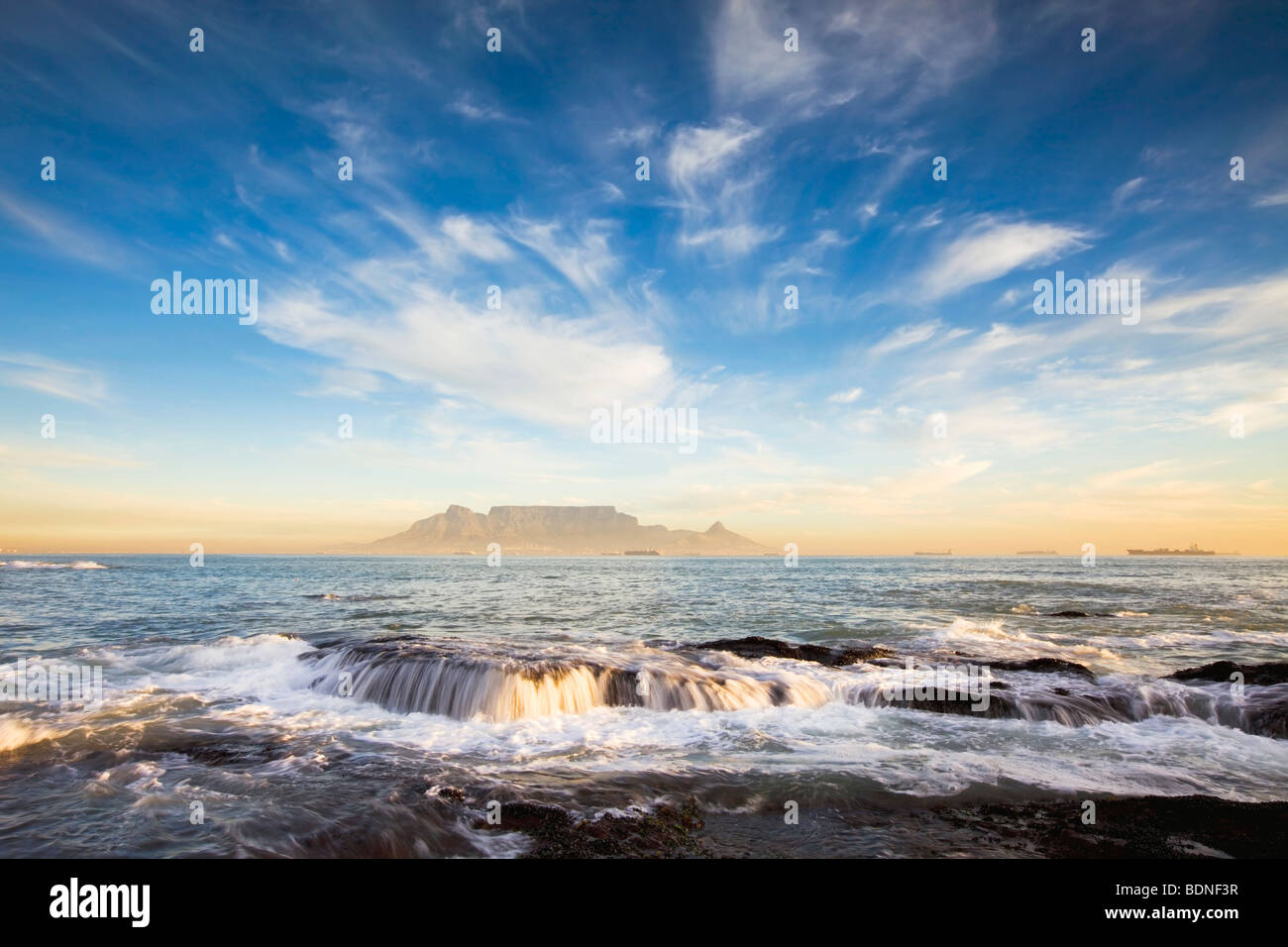 Surf on rocks with Table Mountain in background, Bloubergstrand, Western Cape Province, South Africa - Stock Image