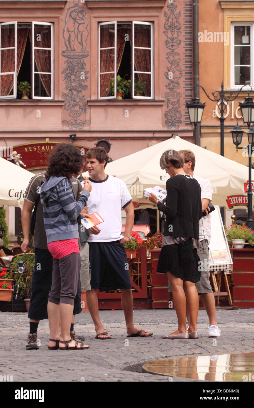 Warsaw Poland young tourists in the Old Town square with open air cafes - Stare Miasto - Stock Image