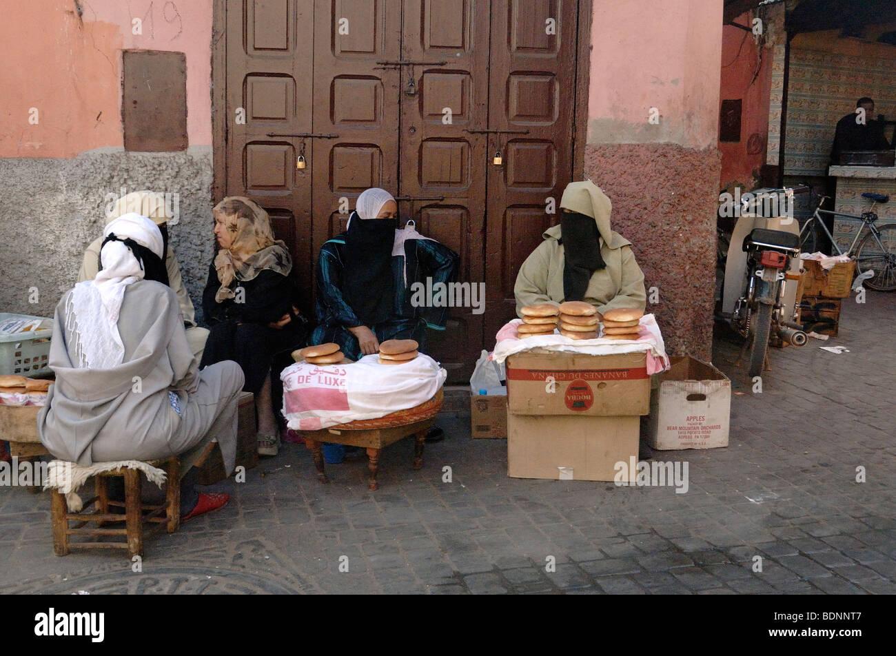 Poor Veiled Moroccan Arabic Muslim Women Selling Bread on the Street in Marrakesh, Morocco - Stock Image