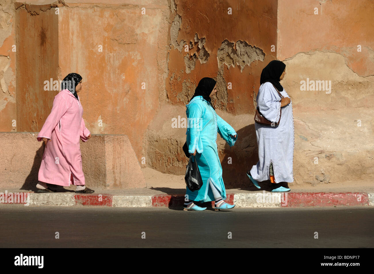 Moroccan Women Wearing Headdresses & Colorful Colourful Costumes Walk Past the  City Walls of Marrakesh, Morocco Stock Photo