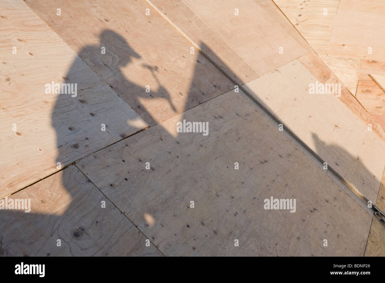 Shadow of carpenter on the roof of an under construction house Stock Photo