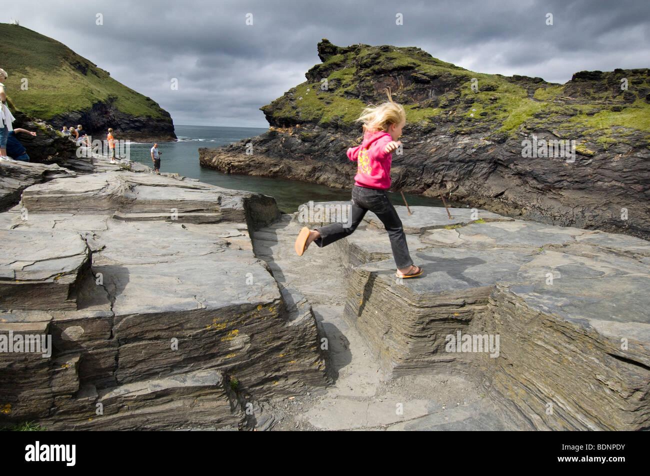A little girl with fair hair jumps across rocks in  Boscastle harbour near Wadebridge, Cornwall. - Stock Image