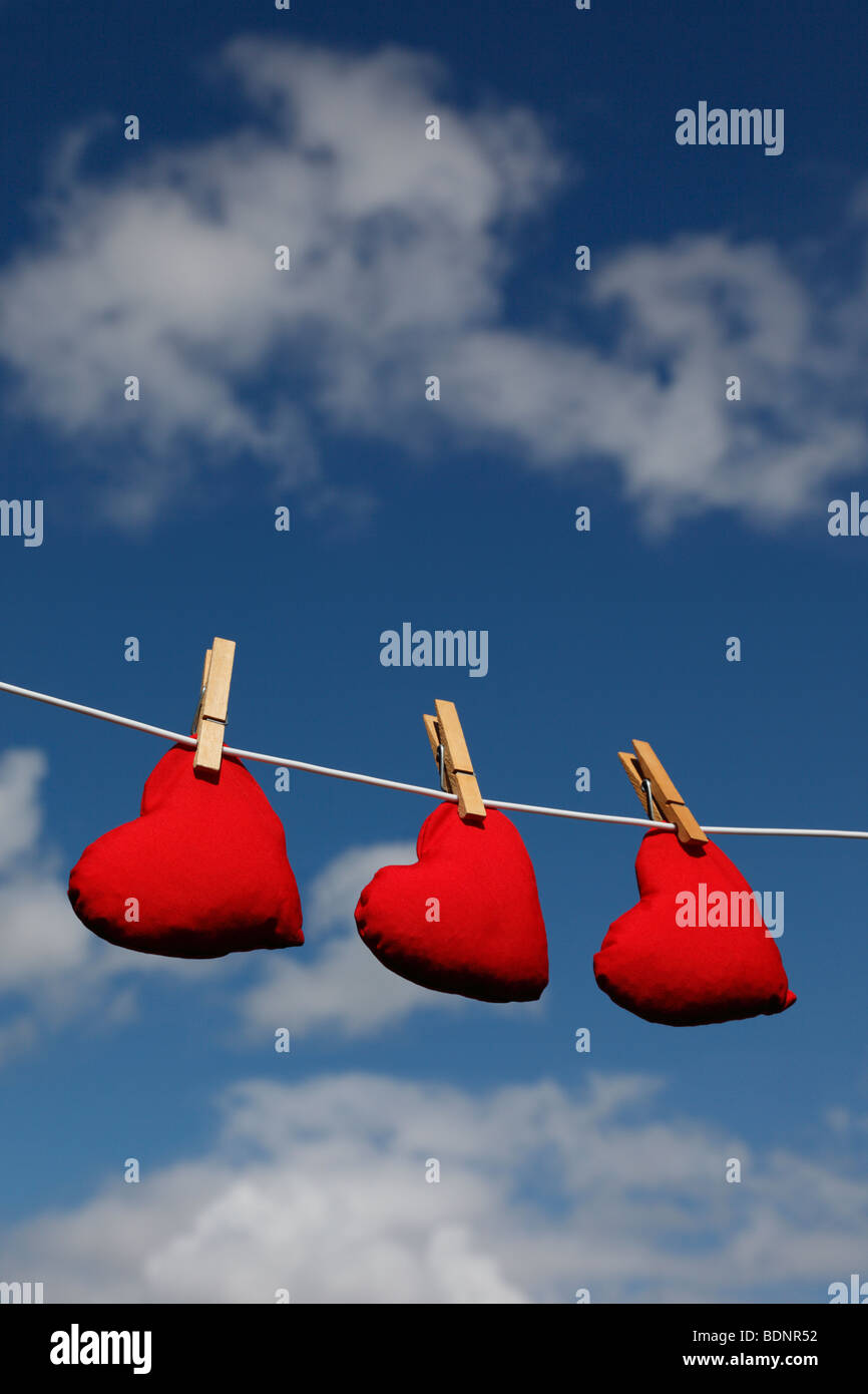 Heart shaped bean bags on a washing line against a summer sky (cloudless version - Ref BDN1TT) - Stock Image