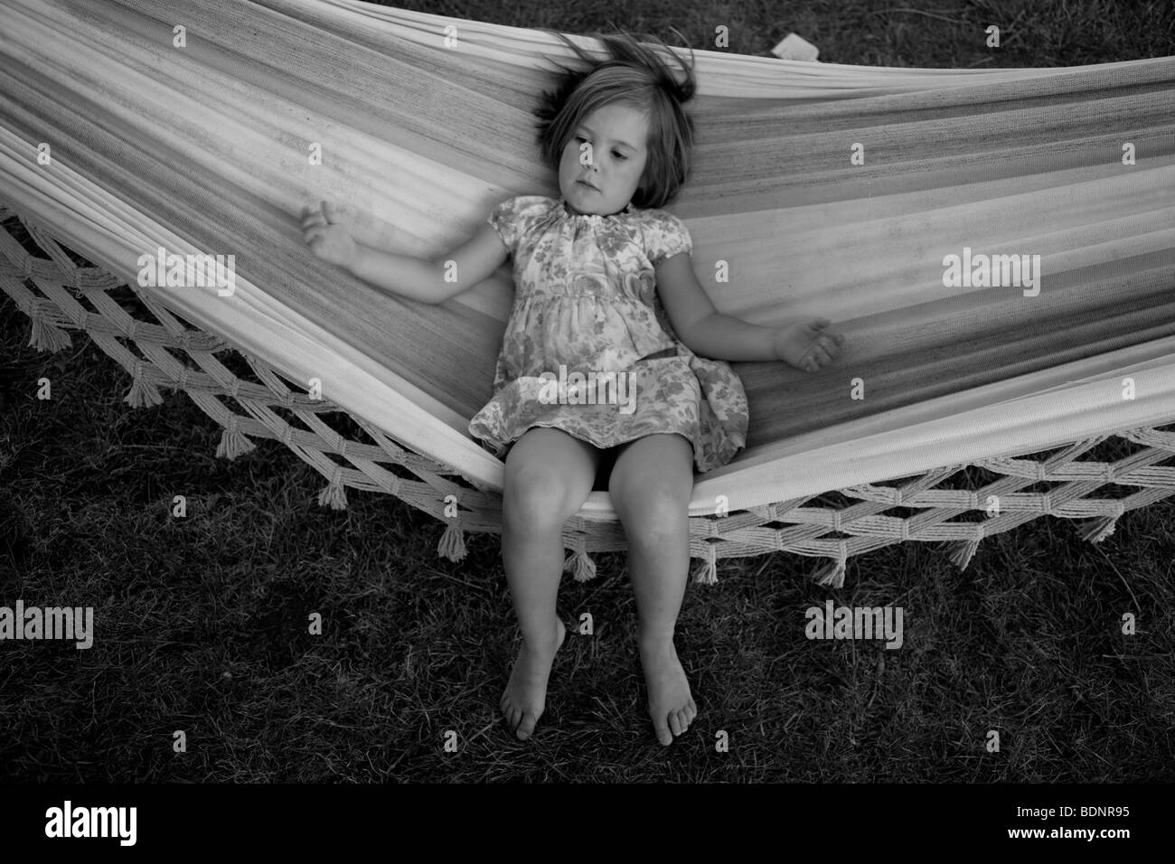 High angle view of young girl in hammock relaxing - Stock Image