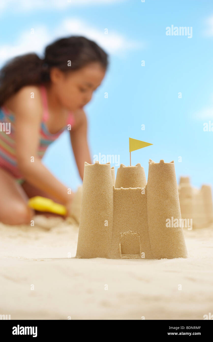 Girl (7-9 years) building sand castles on beach, focus on sand castle in foreground - Stock Image