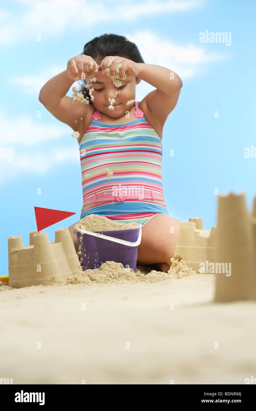 Girl (7-9 years) building sand castles on beach - Stock Image