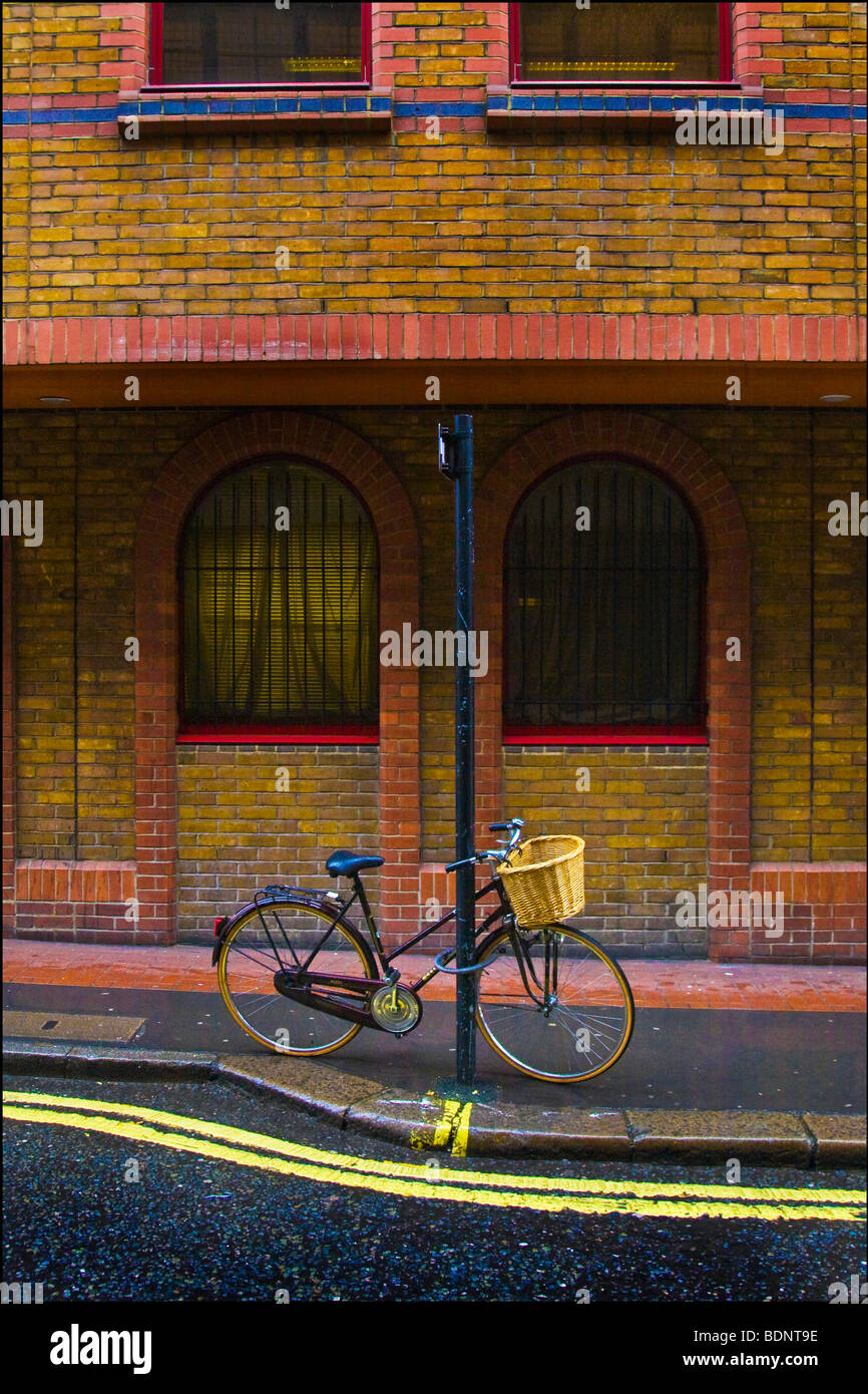 A push bike parked outside a large building - Stock Image
