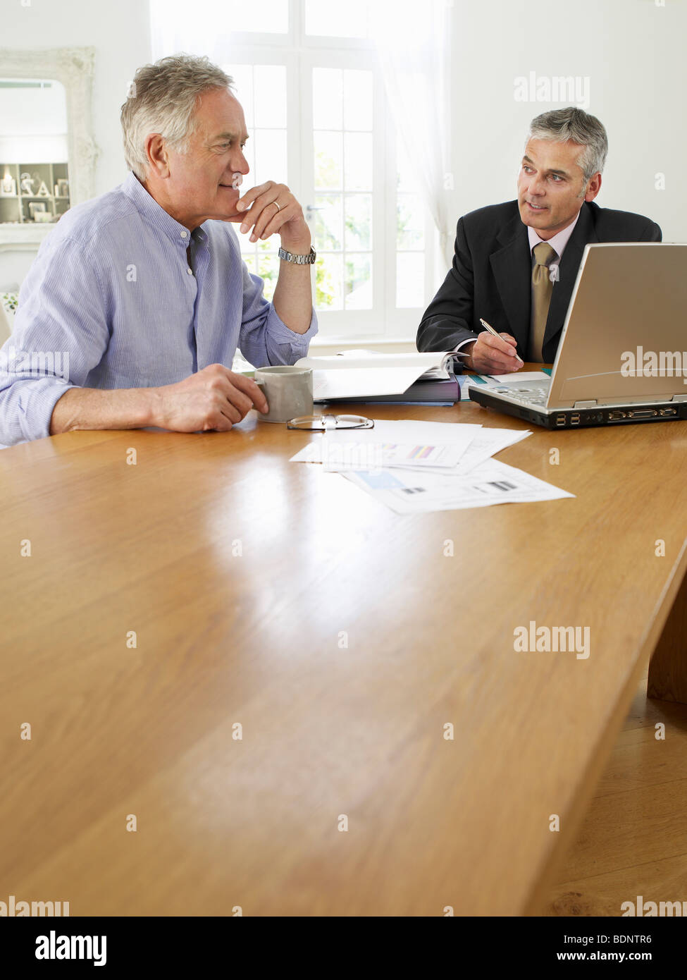 Senior man planning personal finance at home with finacial advisor - Stock Image