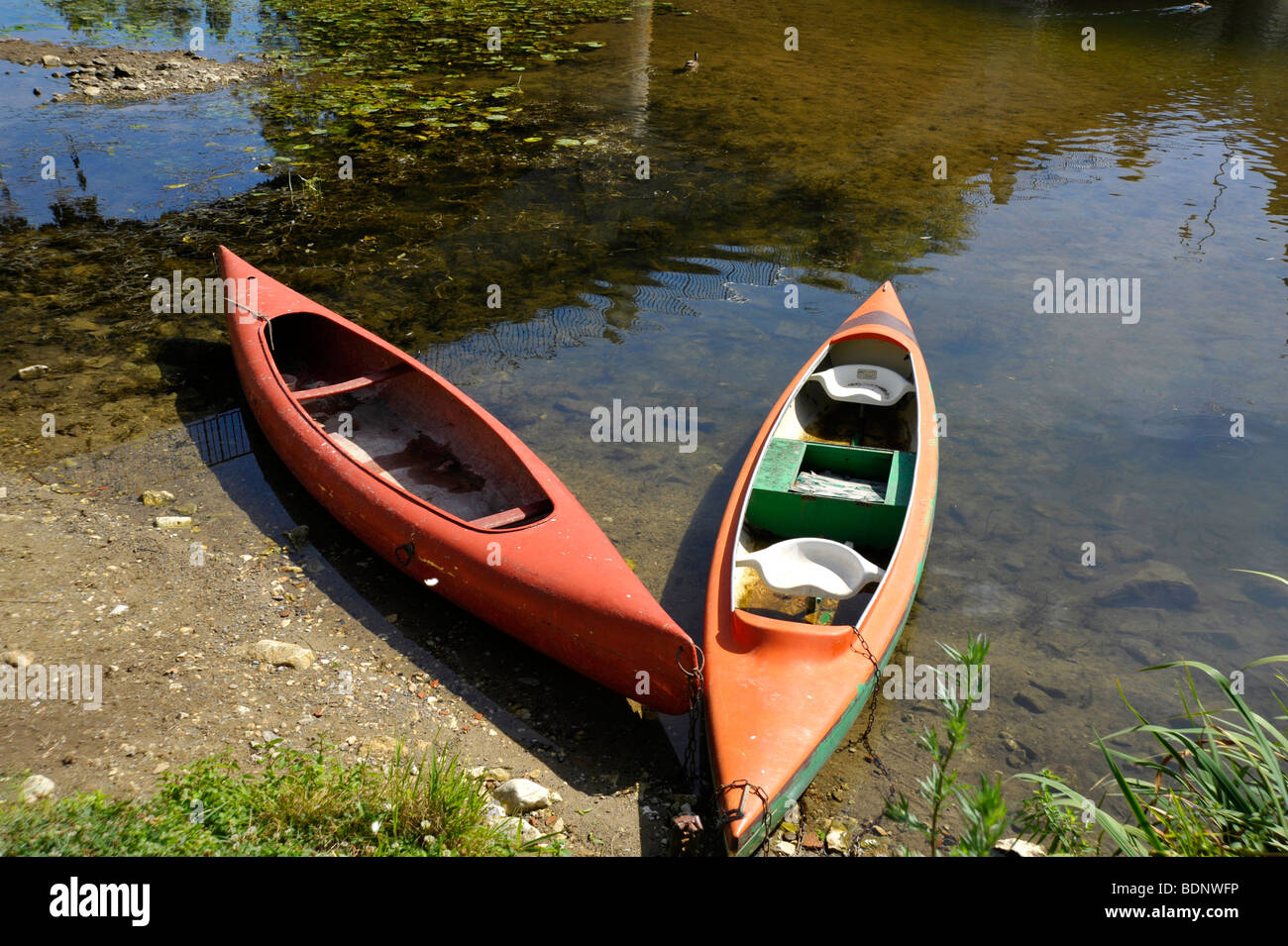 two canoes moored on river bank Stock Photo