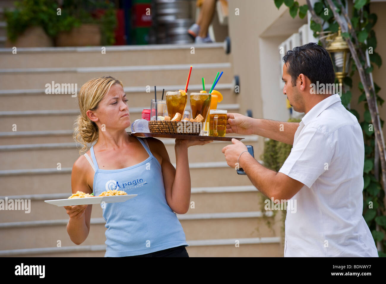 Waiters serving food and drink at restaurant in Fiskardo on the Greek Mediterranean island of Kefalonia Greece GR - Stock Image