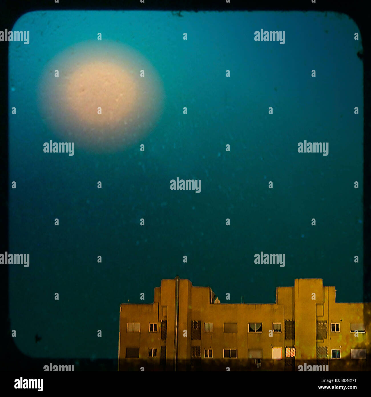 The Moon shining in a blue sky over a block of flats - Stock Image